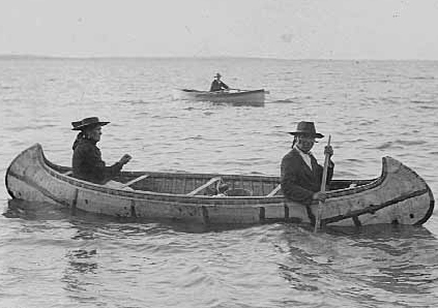 Antique image of Native Americans sharing a canoe in open water.