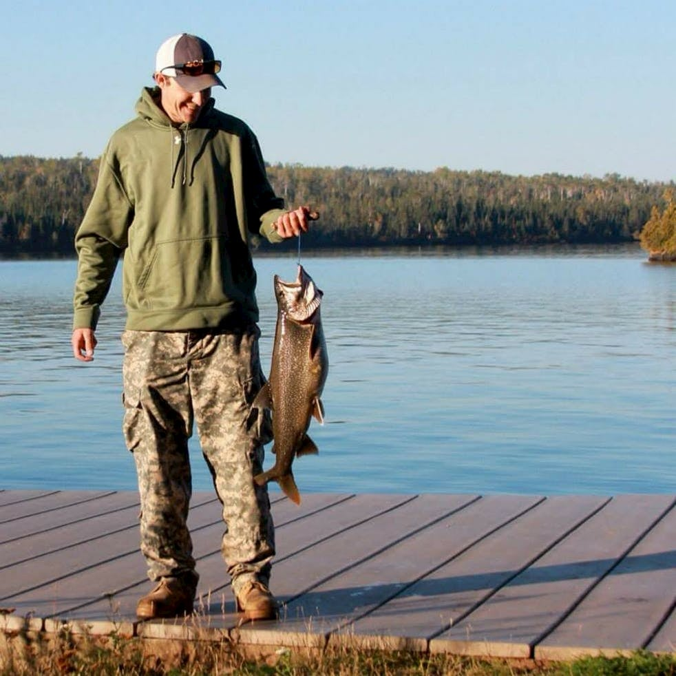 Man styanding on dock in front of lake holding large fish on a hook.