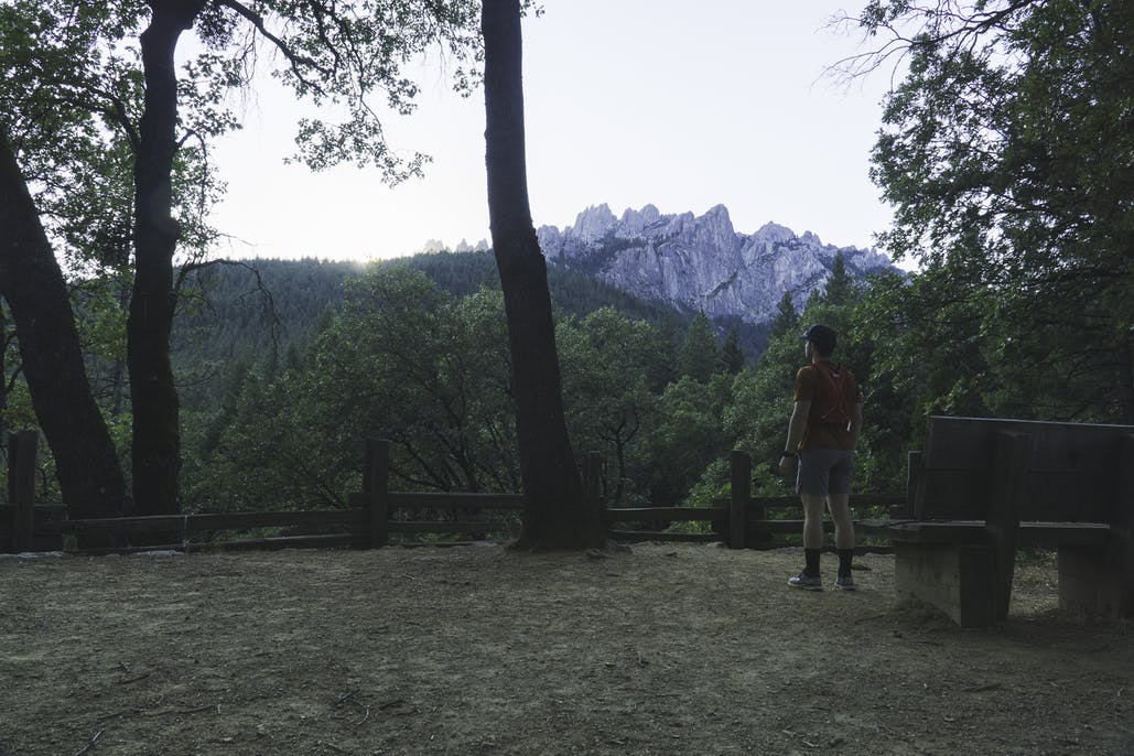 person standing next to picnic bench looking at castle crags