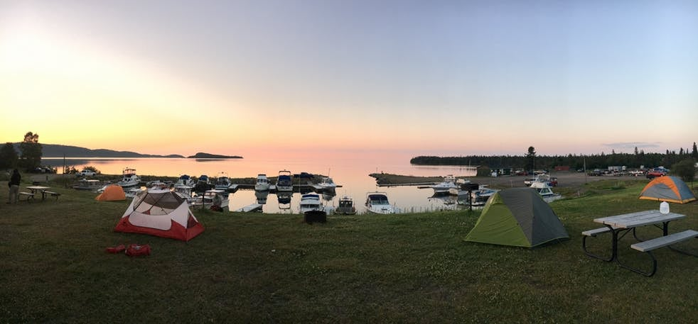 Sunset over a large lake with boats docked and tents setup on the shore.