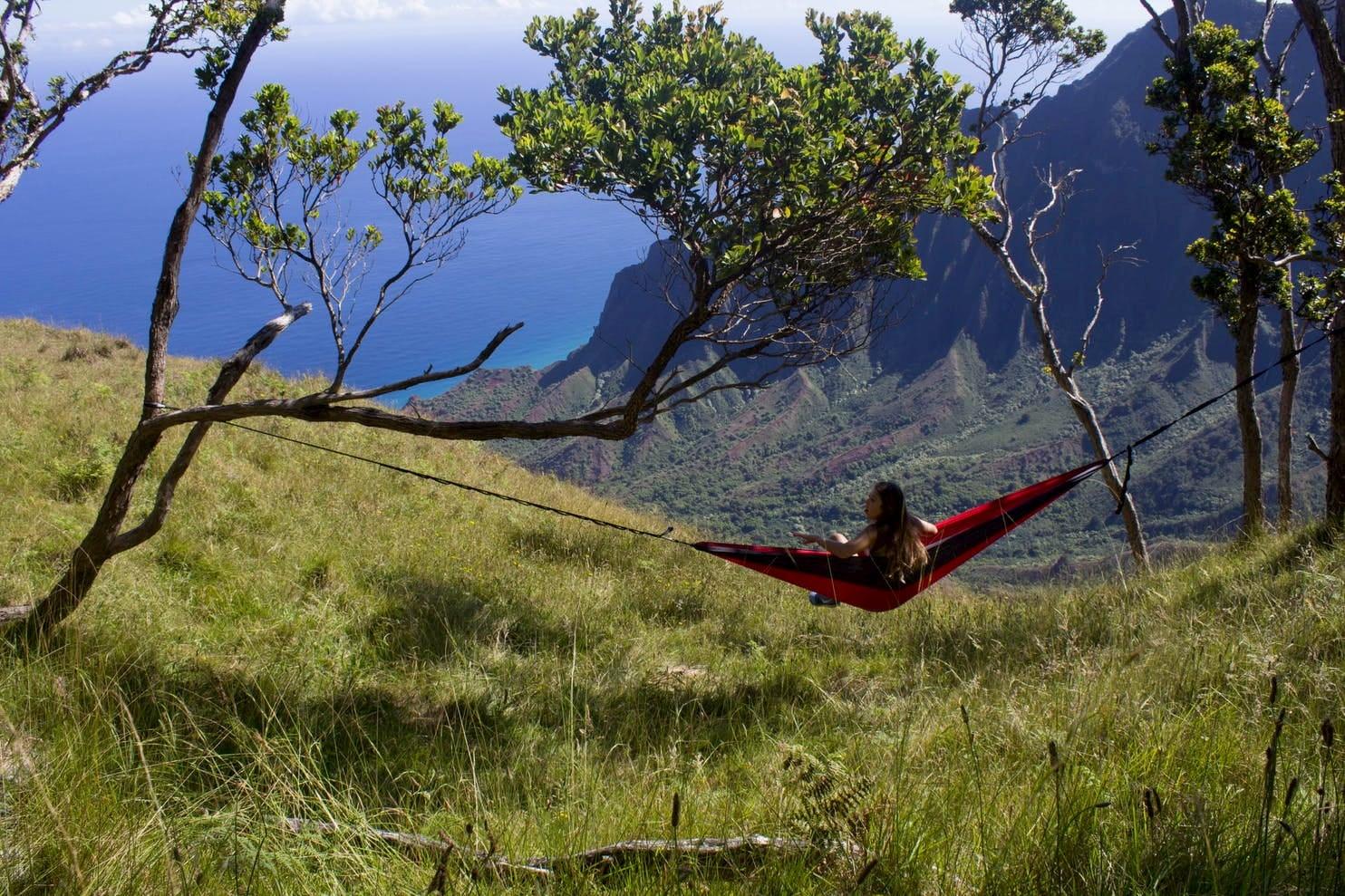 Women sitting in a hammock between two tree branches in field overlooking the ocean below.