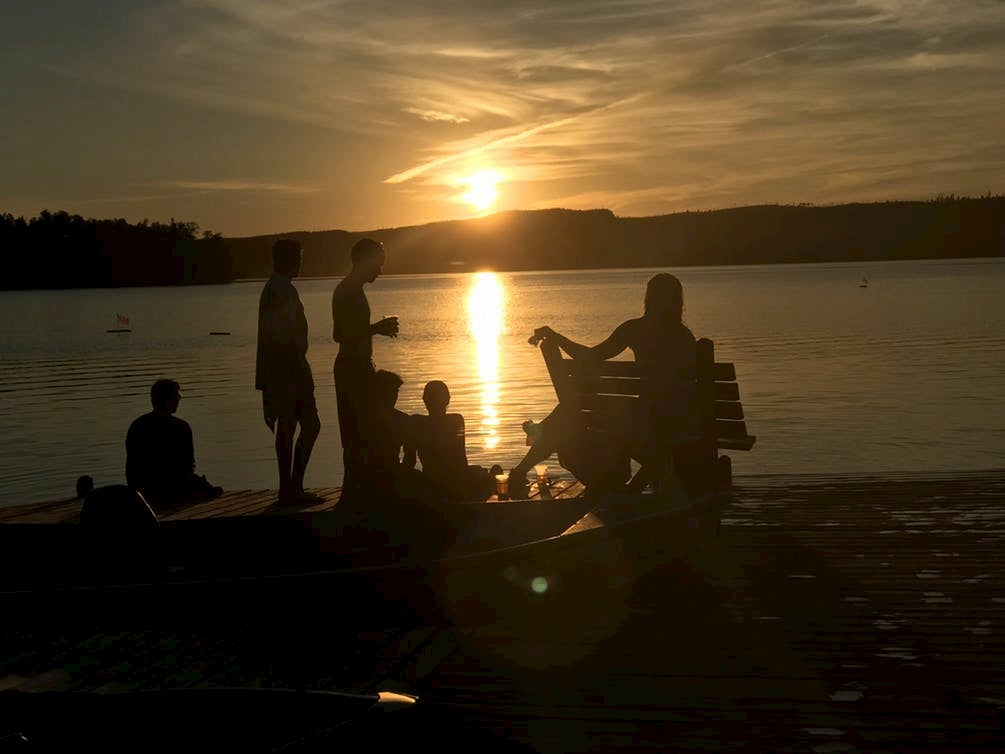 Silhouettes of a group of people on a lakeside beach during sunset.