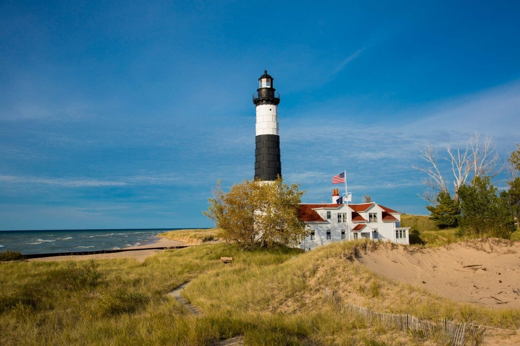 Black and white striped lighthouse in beach dunes on the coast.