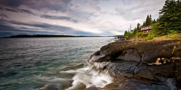 Waves crashing against the coast of a forested island.