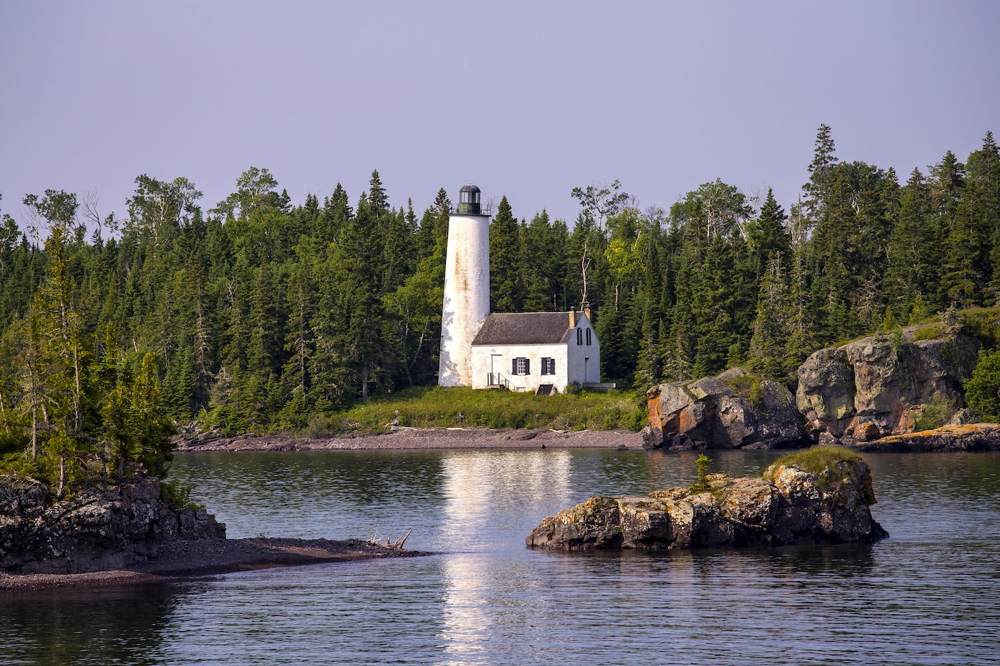 White lighthouse on the coast of a forested island.