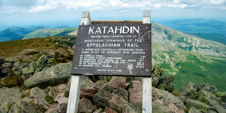 """Kathadin"" sign on top of mountain surrounding by green alpine landscape."