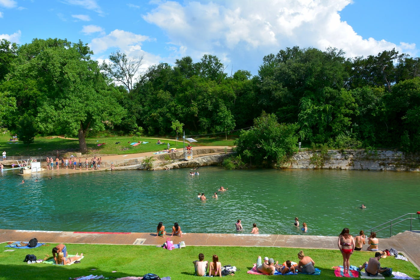 Outdoor pool surrounded by bathers.