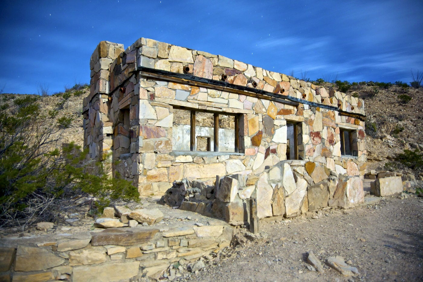Stone building in the desert with hollow windows.