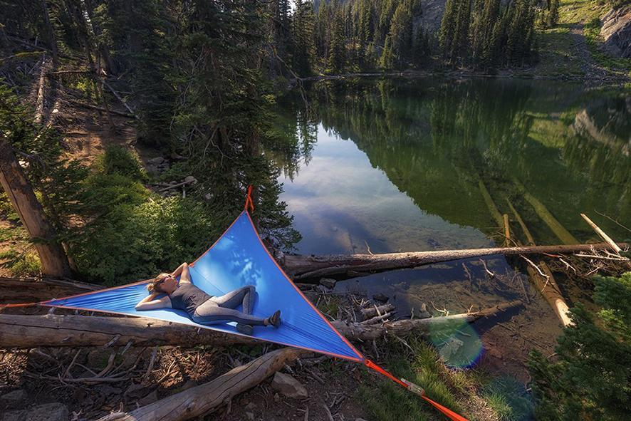 Person sleeping in a tent over a lake