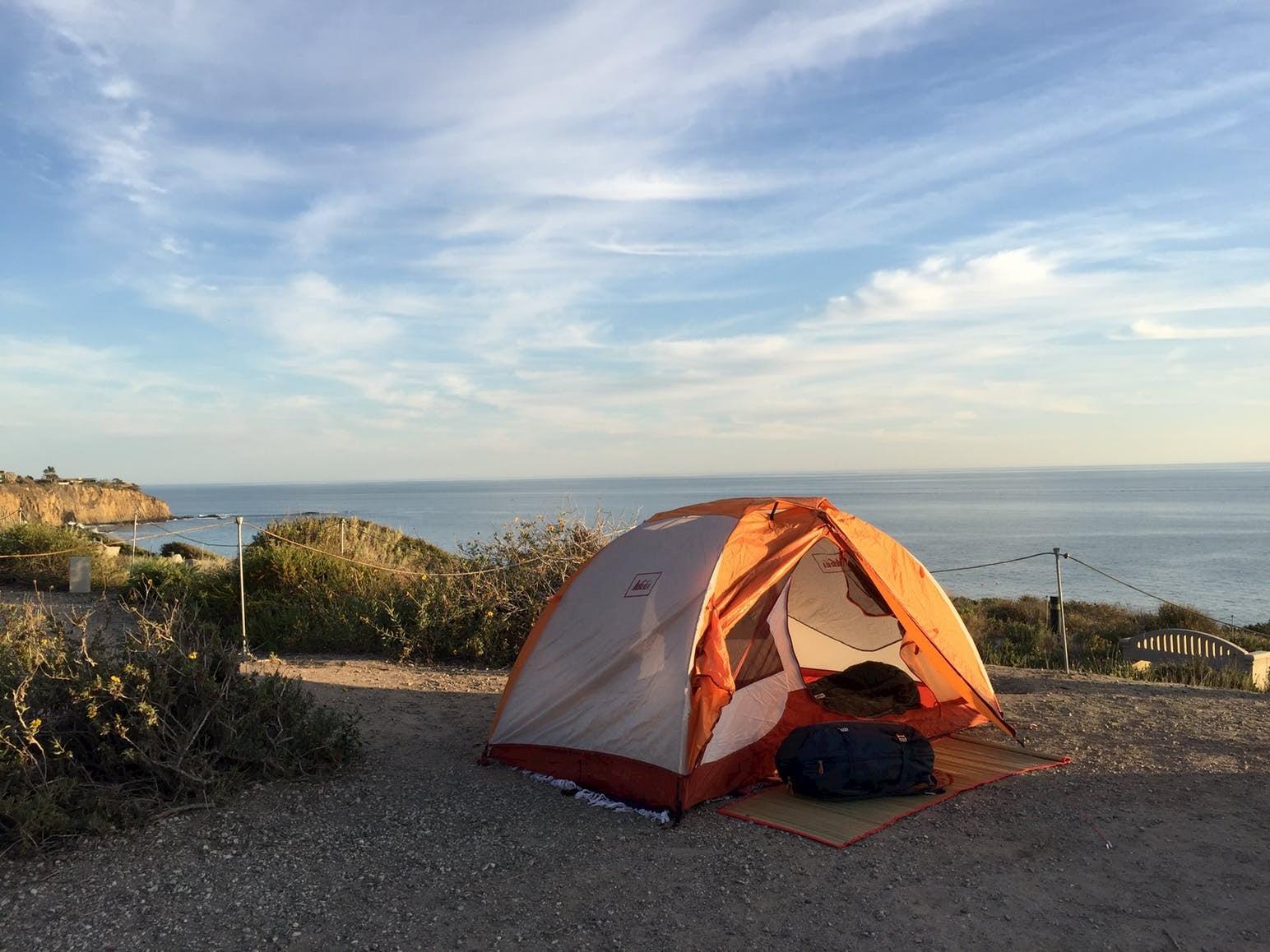 Orange tent setup at coastal campsite.