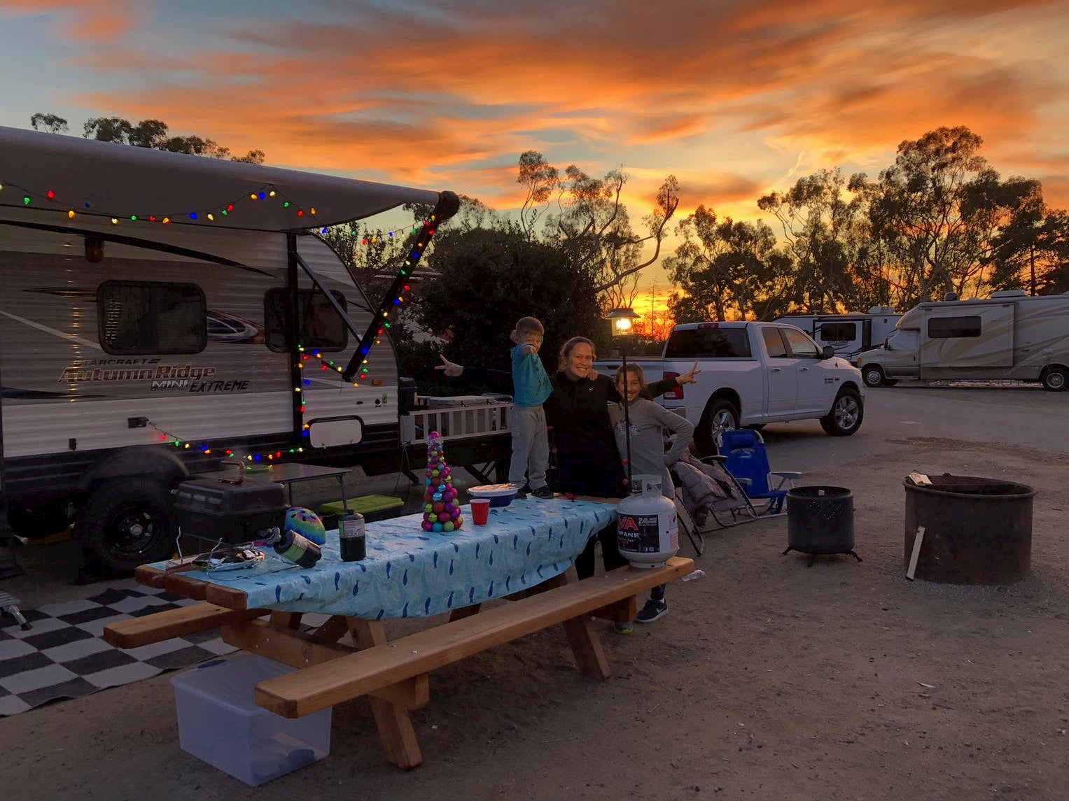 Family posing beside picnic table while the sun sets over RV campground.