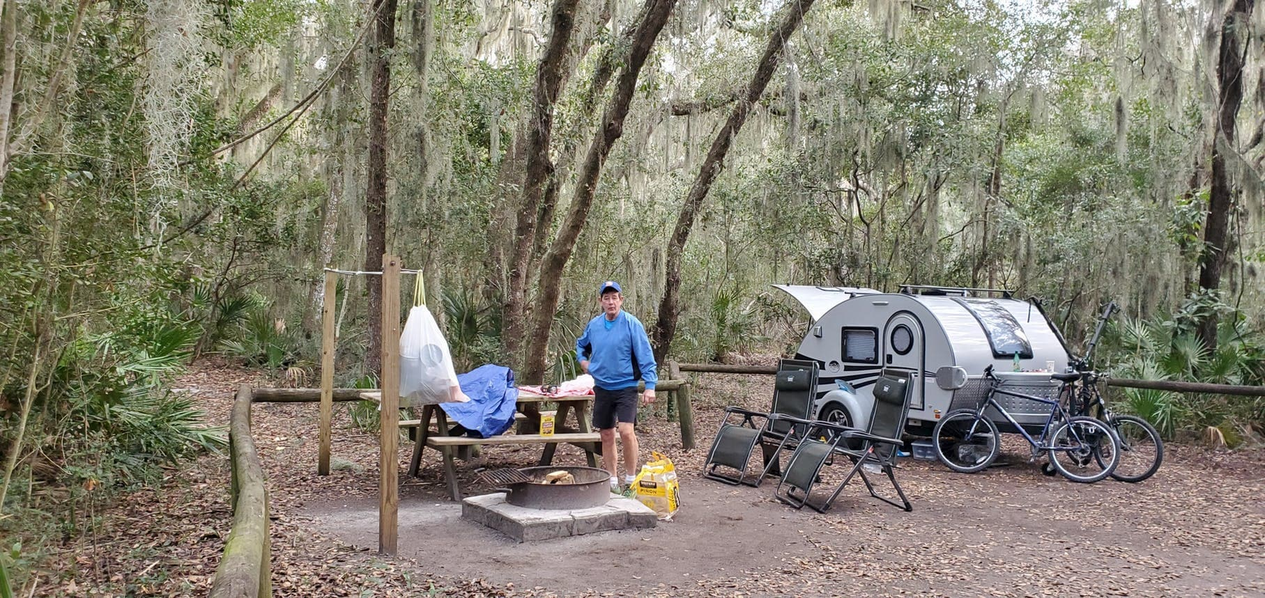 Man beside a teardrop trailer in mossy forested campsite.