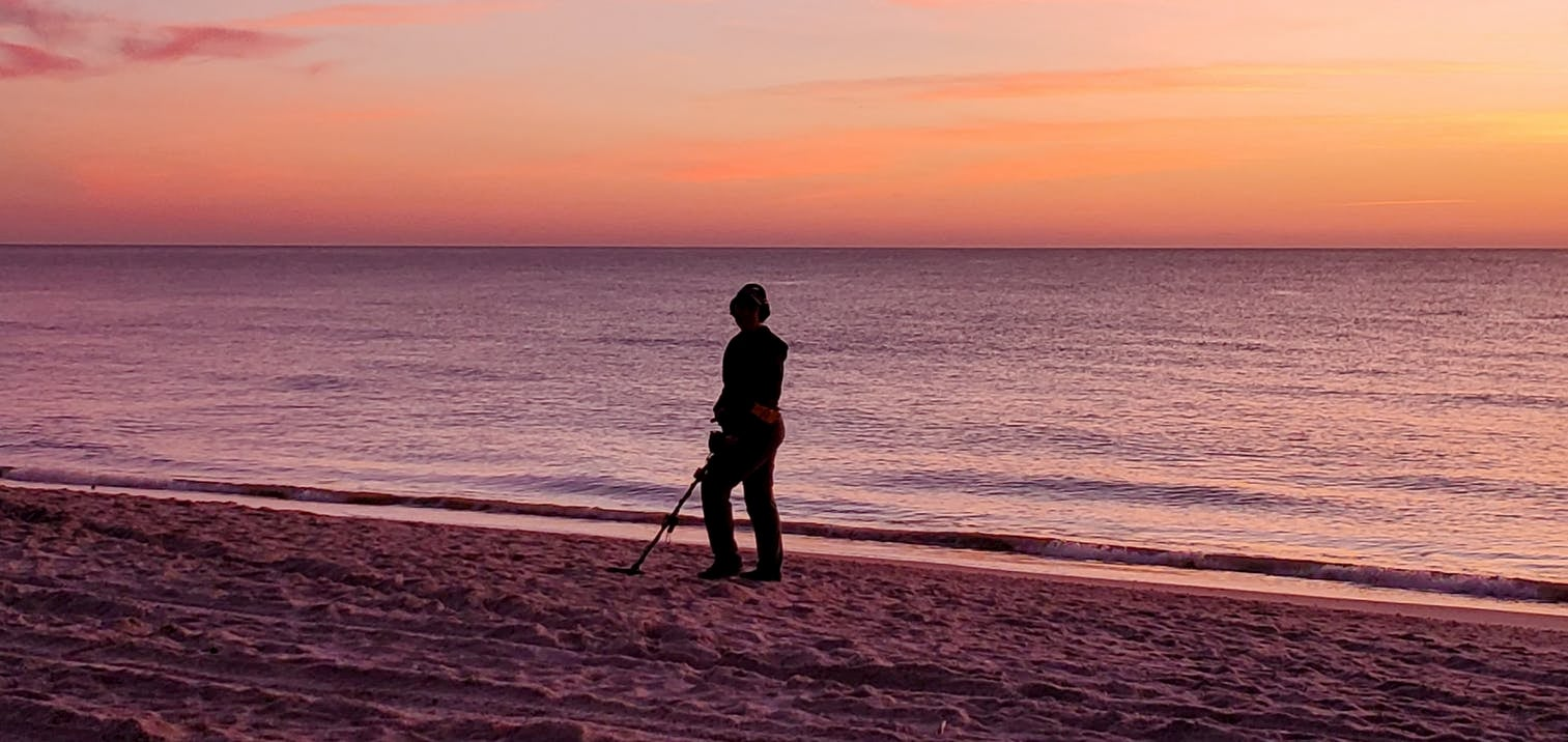 Person using metal detector during sunset on the beach.
