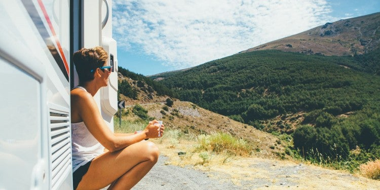Woman drinking coffee outside of RV