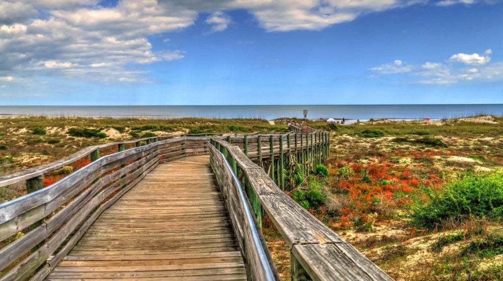 Wooden boardwalk leading to the coast surrounded by san dunes on Amelia Island.