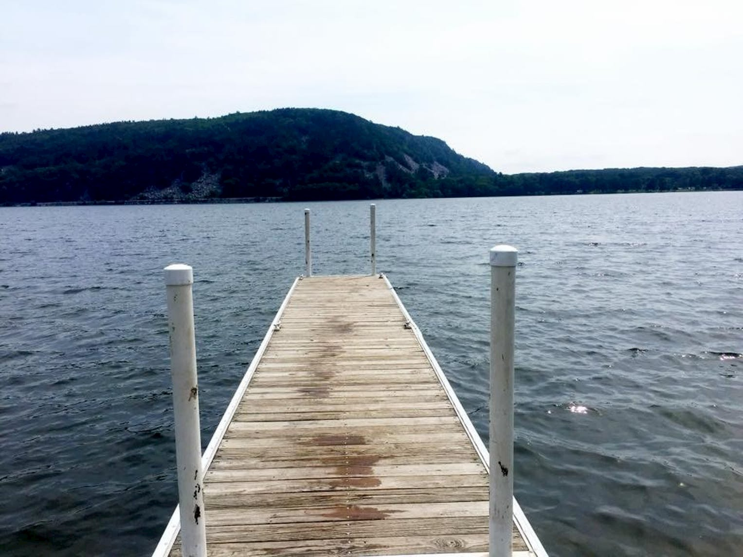 Dock stretching out towards a lake surrounded by mountains.