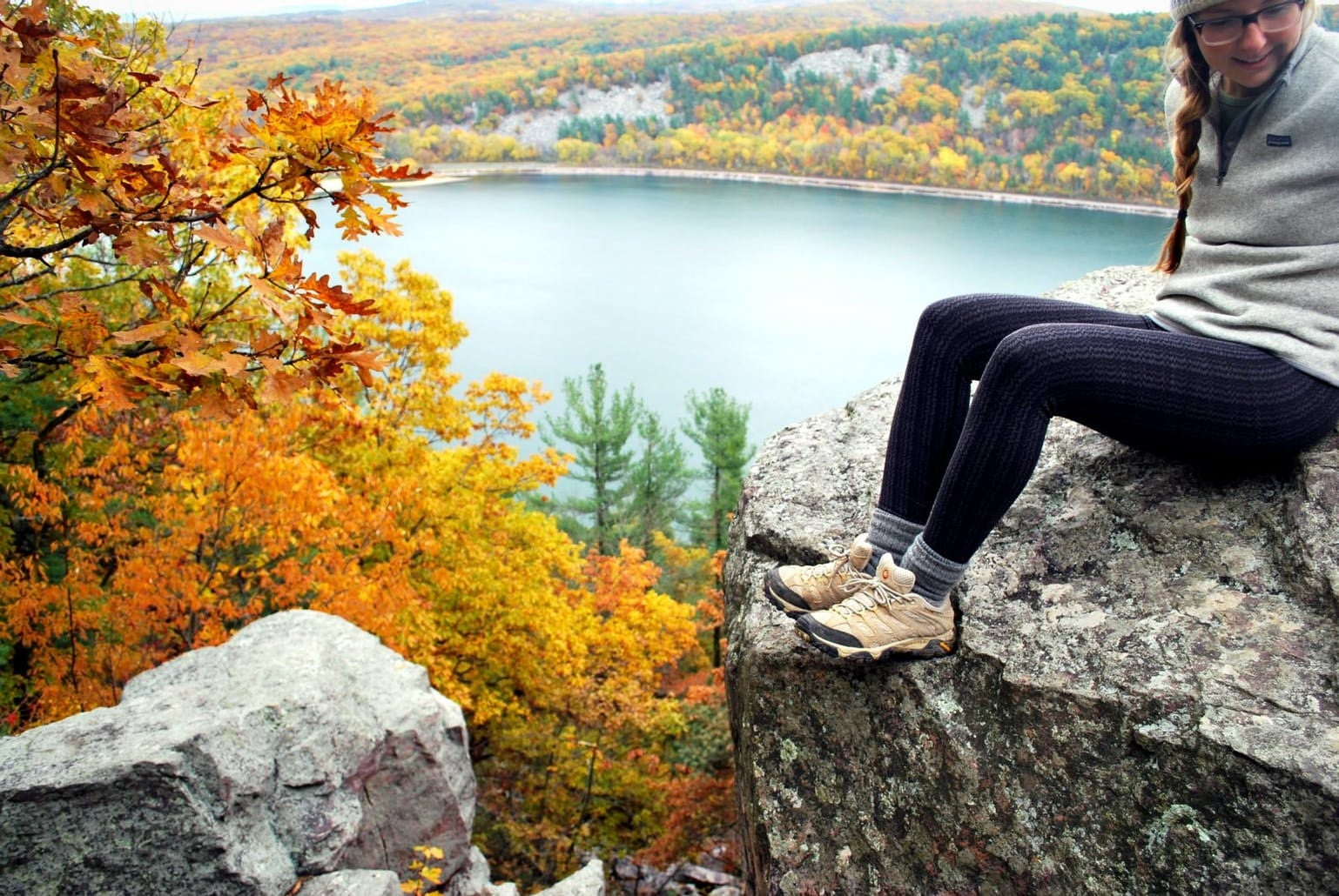 Girl in hiking clothing posing in front of view of blue lake and fall foliage.