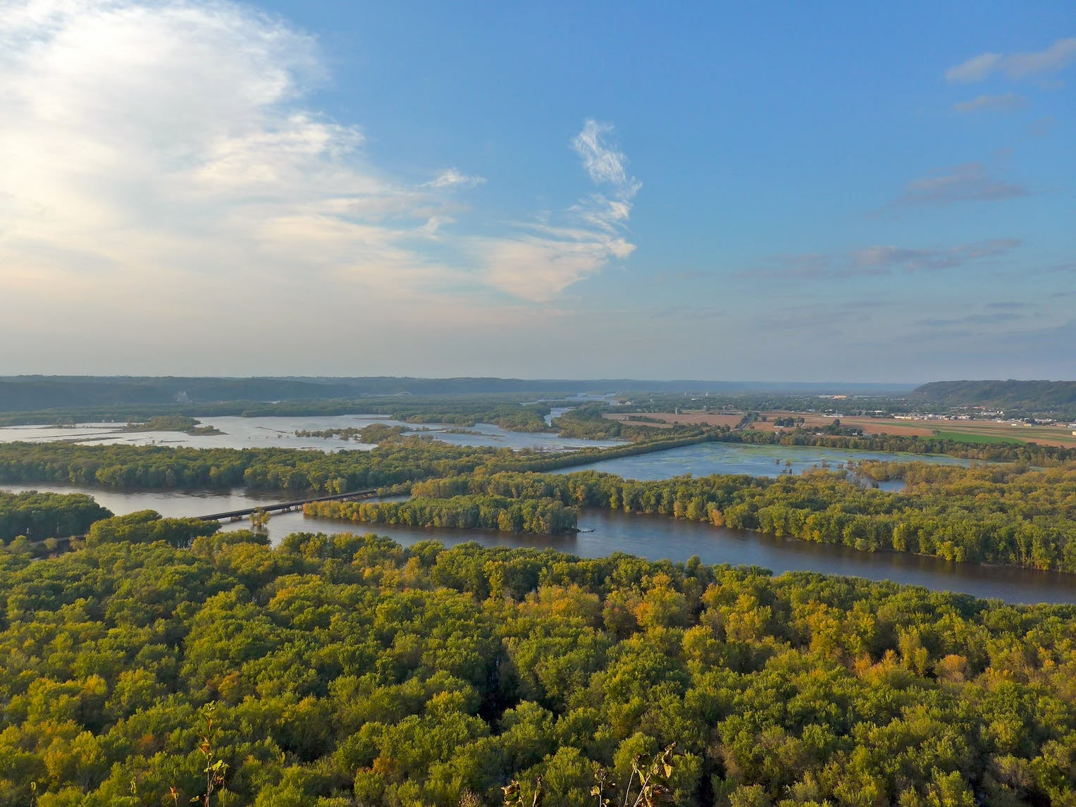 View overlooking lakes surrounded by forests under a blue sky.