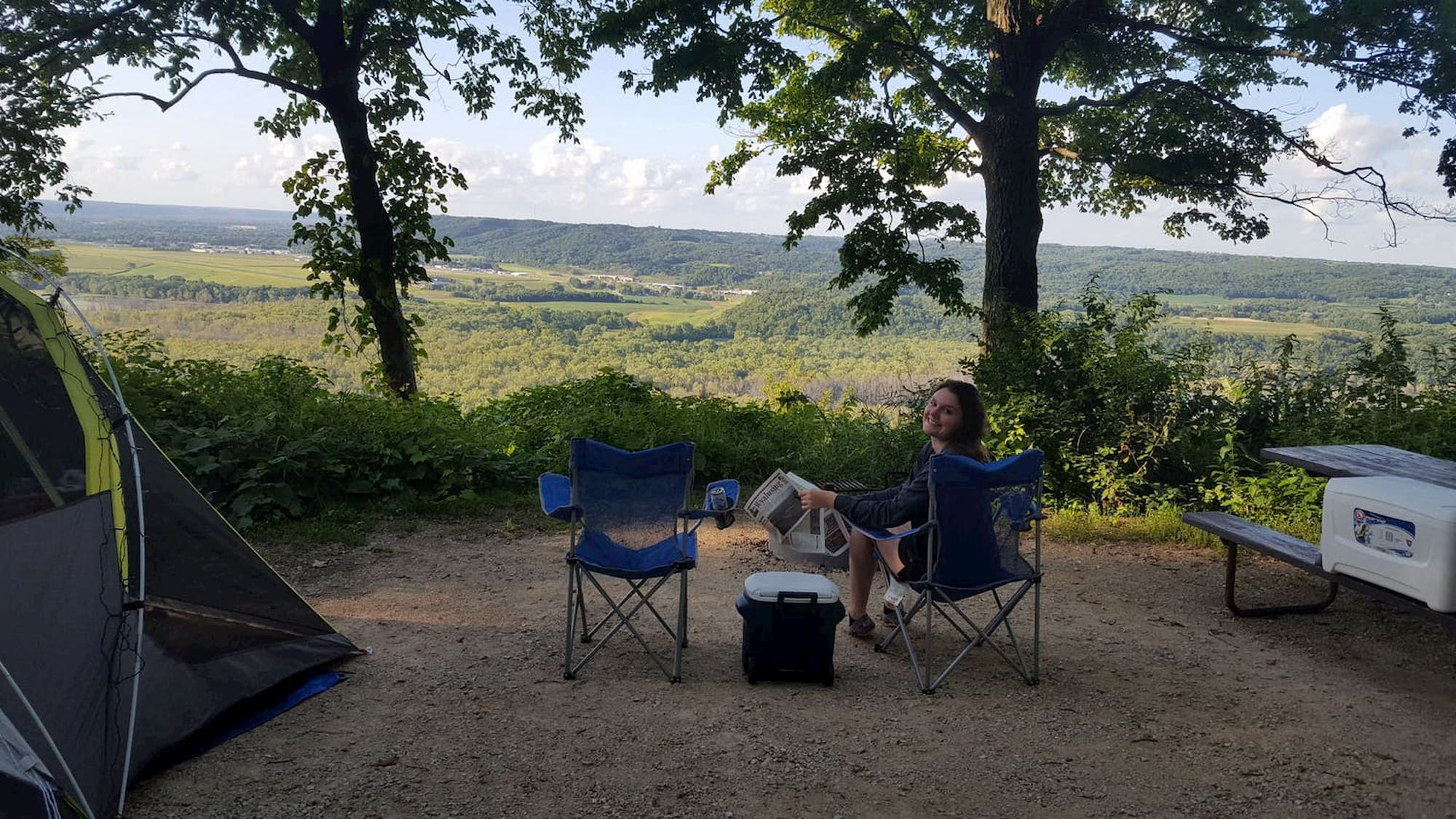 Women relaxing in camp chair ion shaded area in front of large panoramic view of a valley