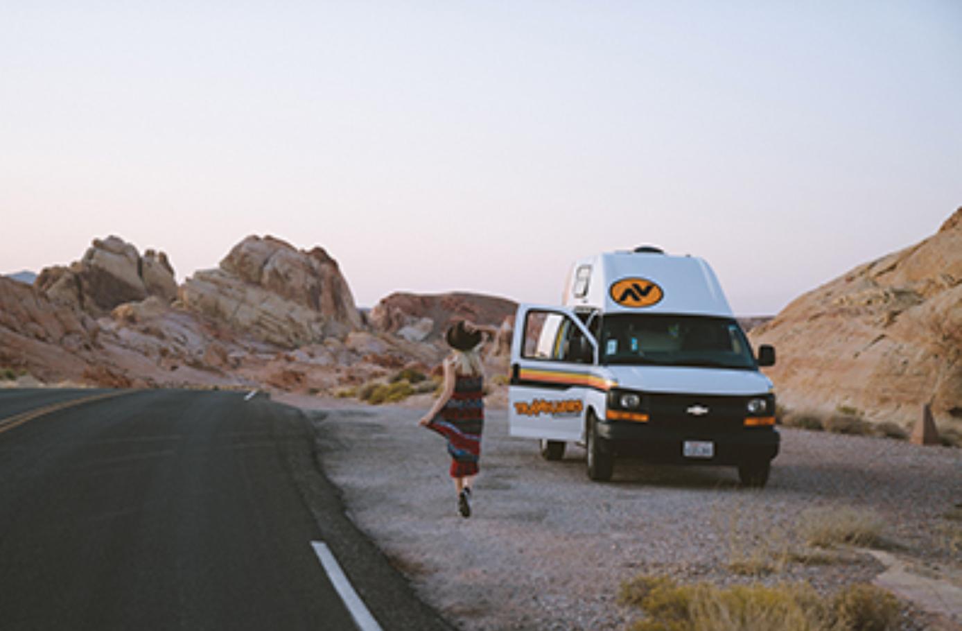 Women running towards van in the desert.