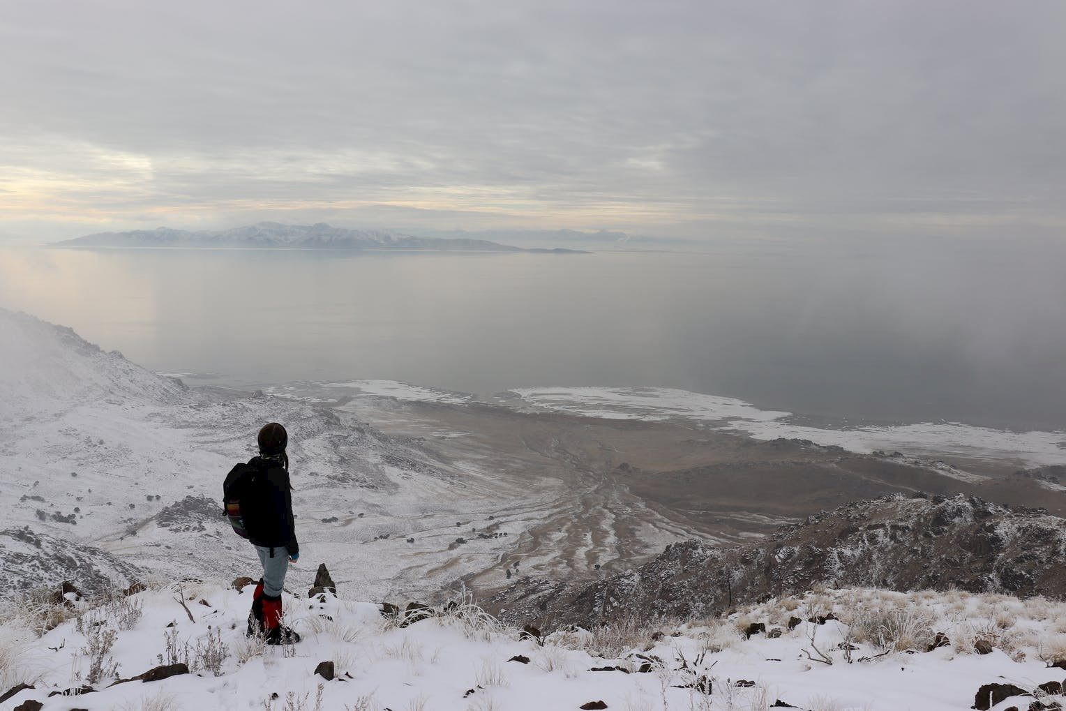 Hiker in gaiters and winter clothes overlooking snow dusted island from a hilltop.