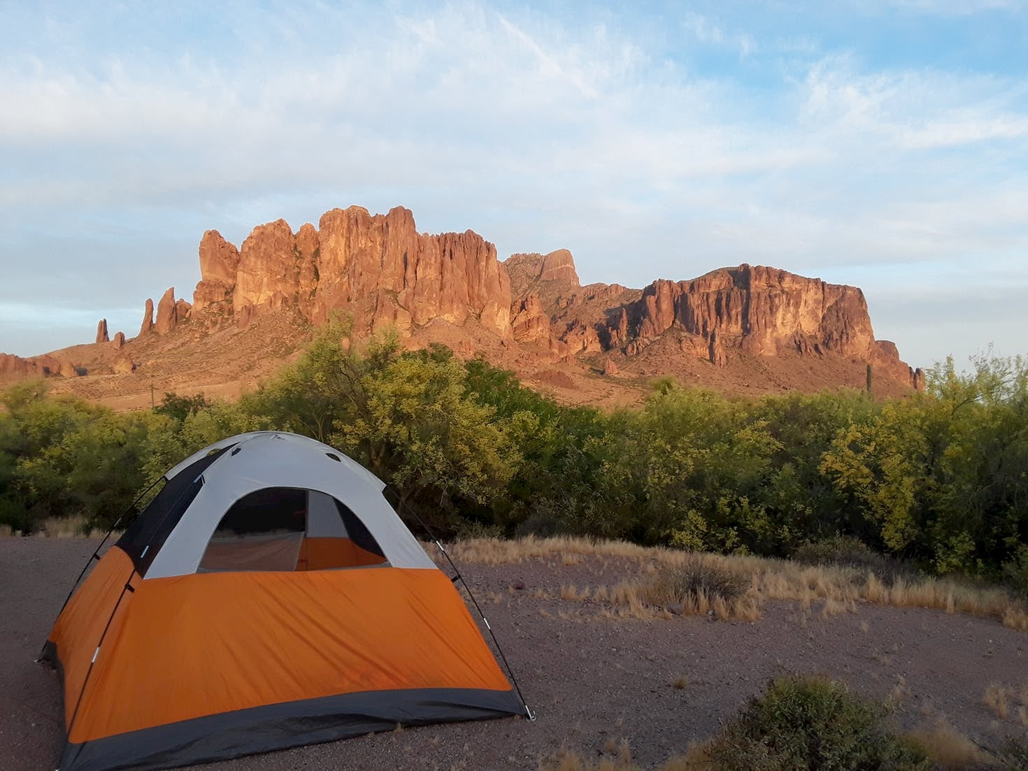 Orange tent set up in front of the Superstition Mountains in Arizona.