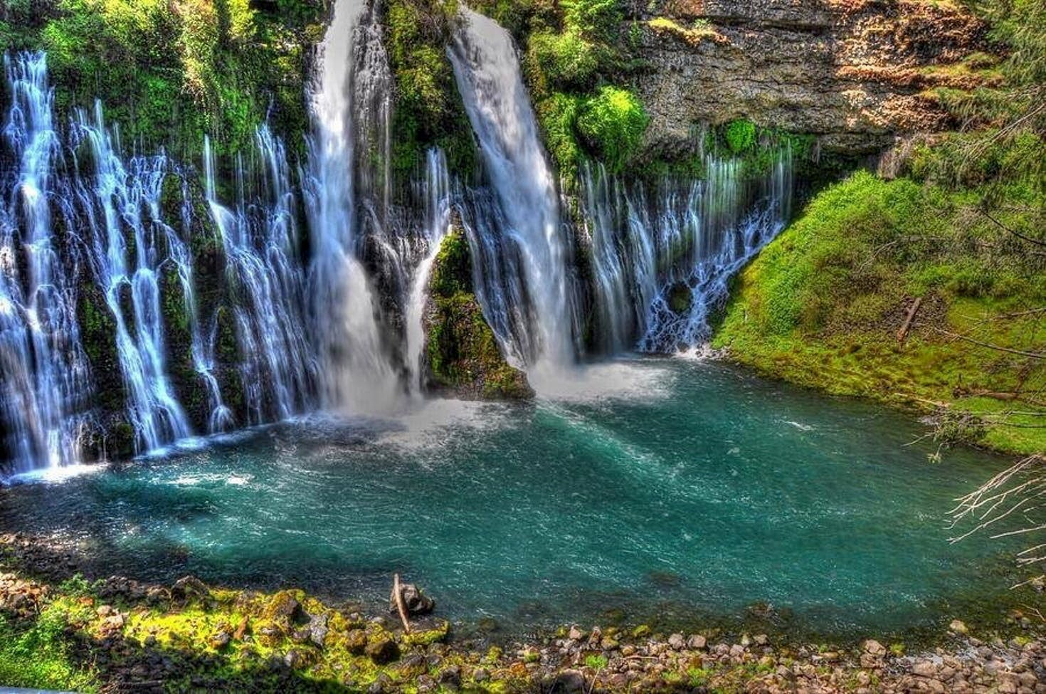 Cascading blue waterfalls surrounded by lush green grass.