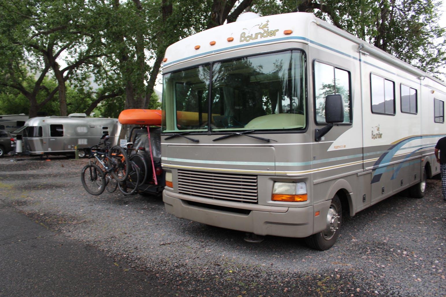 RV parked beside car with bike rack and kayak strapped to it in a gravel RV park.