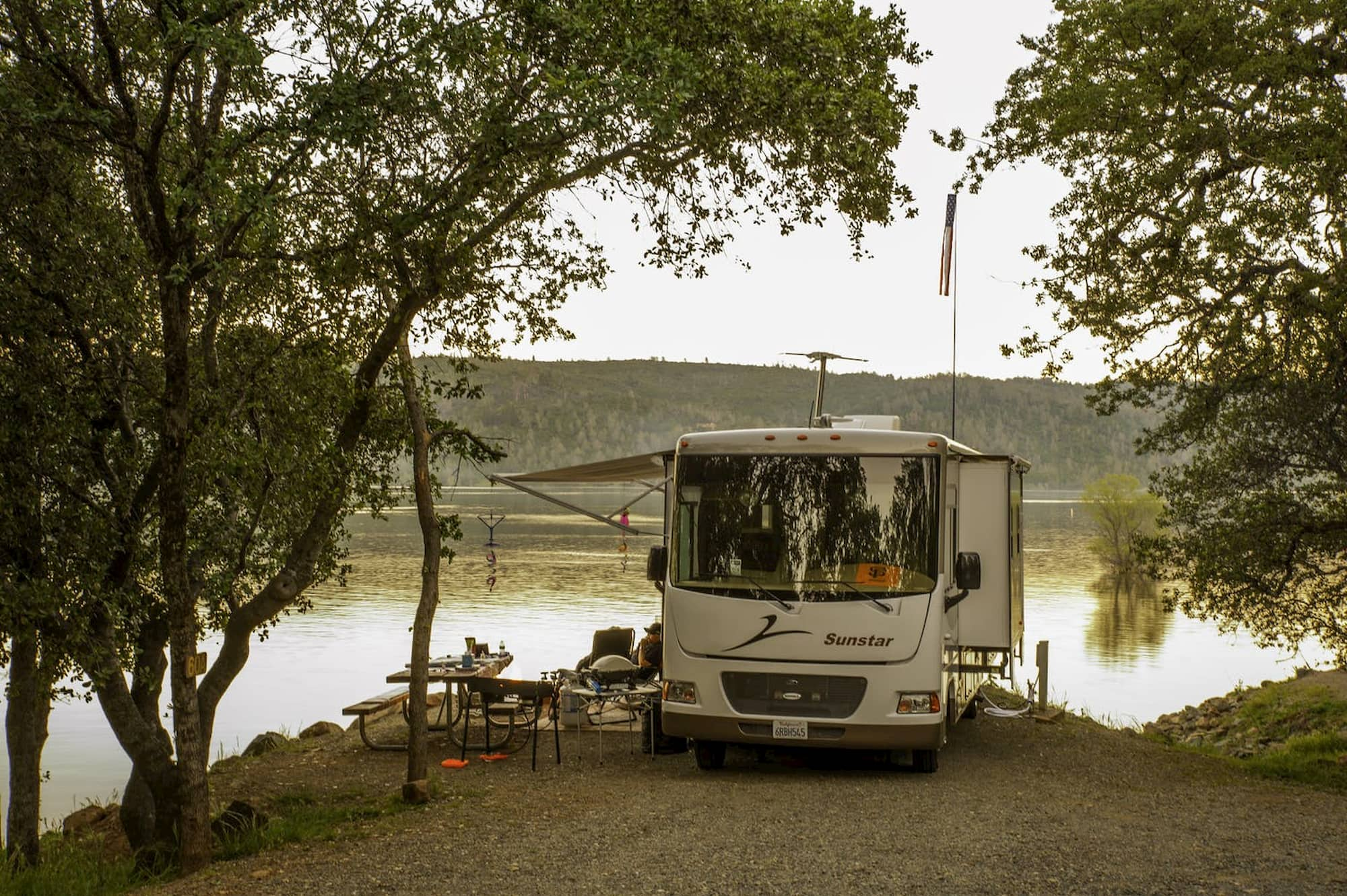 Camper parked beside water with people outside lounging in camp chairs.