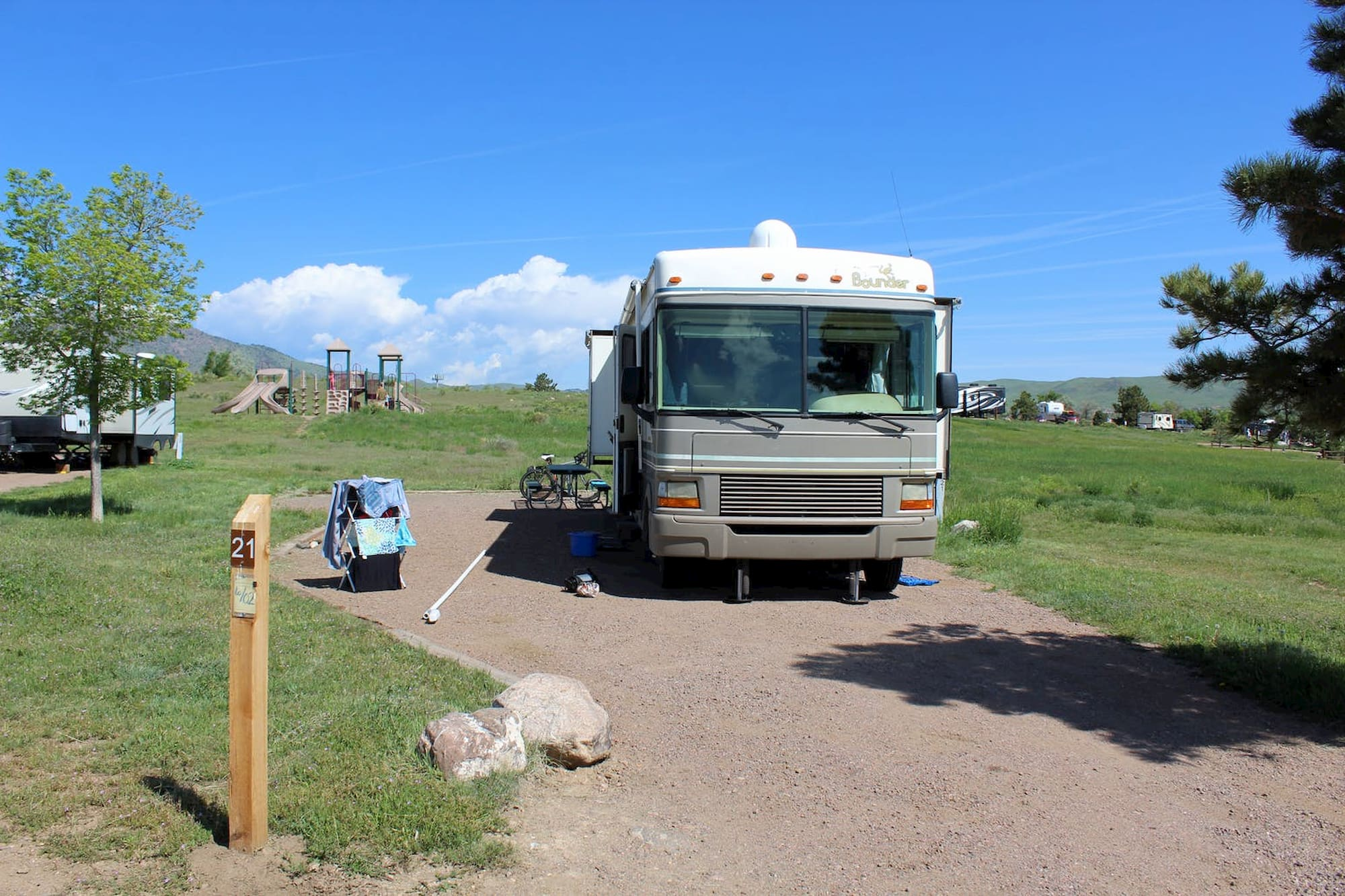 RV parked in gravel space beside lush green field on a clear sunny day.