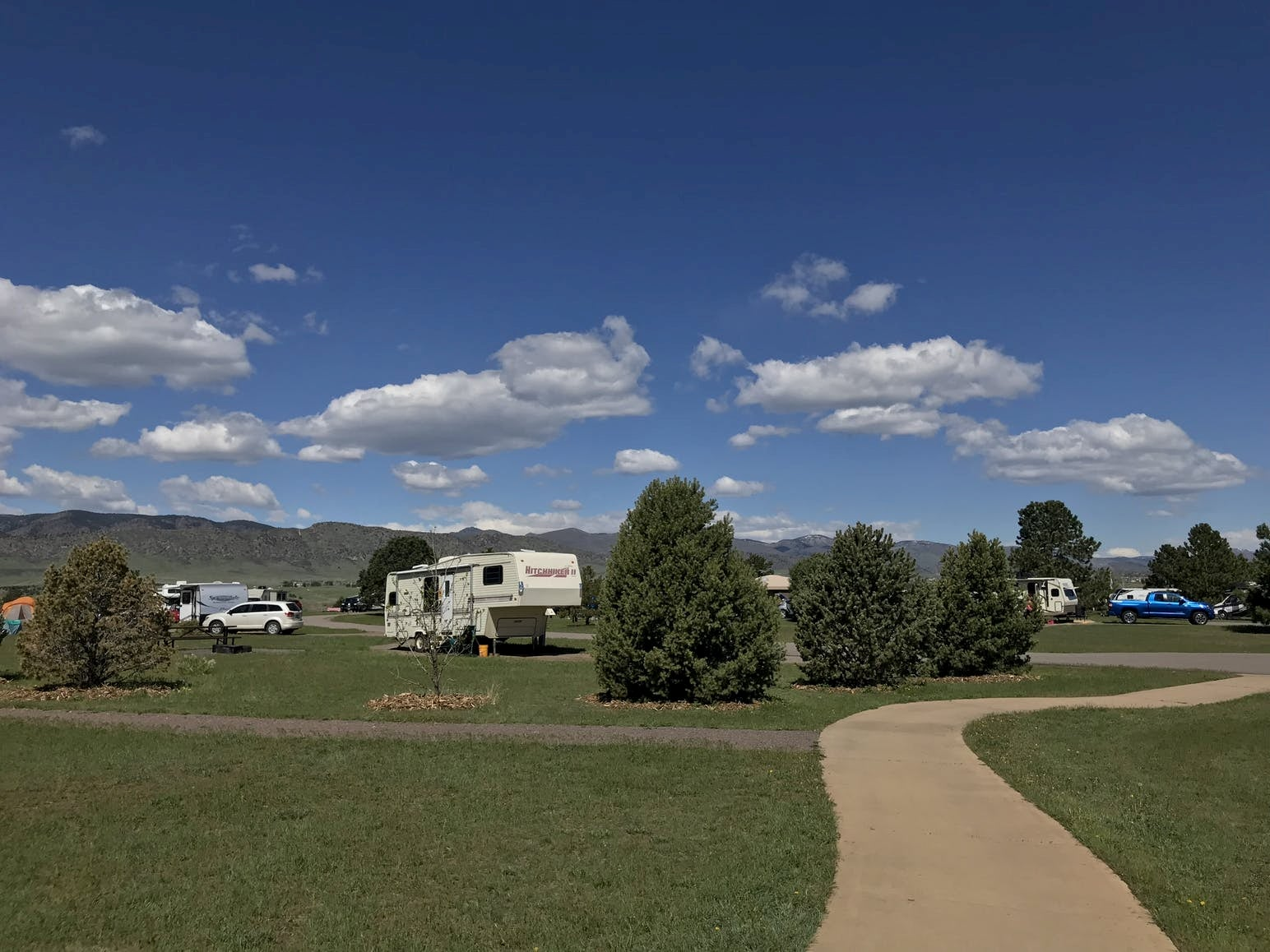 RV park surrounded by curving walkway and field of grass on a bluebird day.