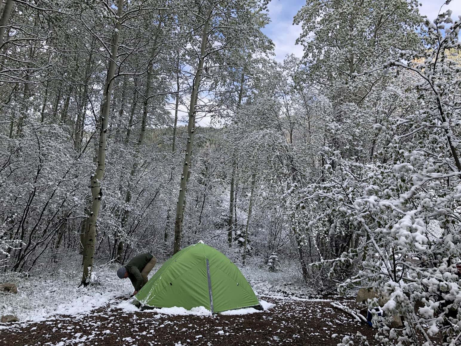Snow dusted forest surrounds man setting up green tent in the foreground.