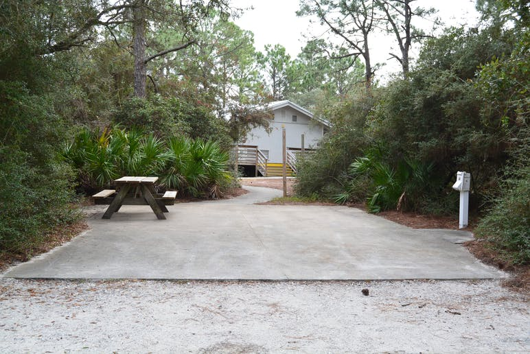 picture of empty rv site with picnic table and showerhouse in the background