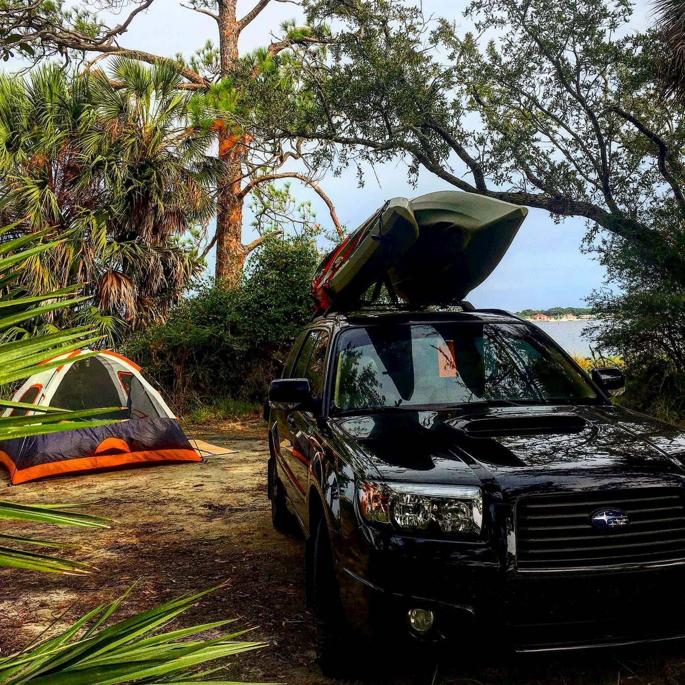 Black SUV with kayak on top parked next to tent at coastal campsite.