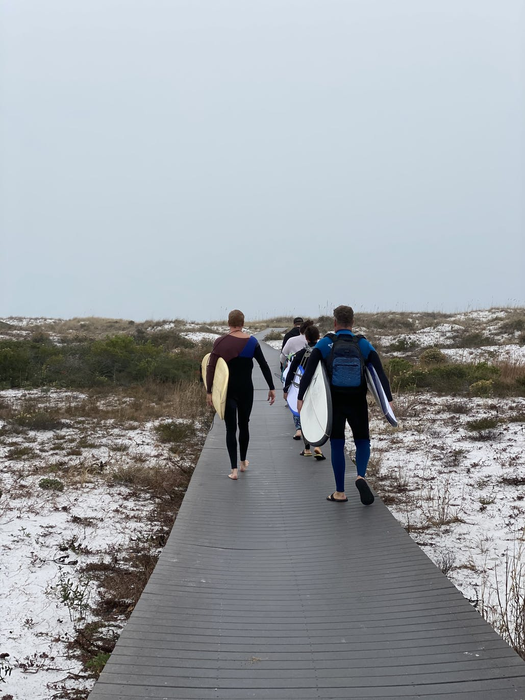 surfers walking to beach at fort pickens campground