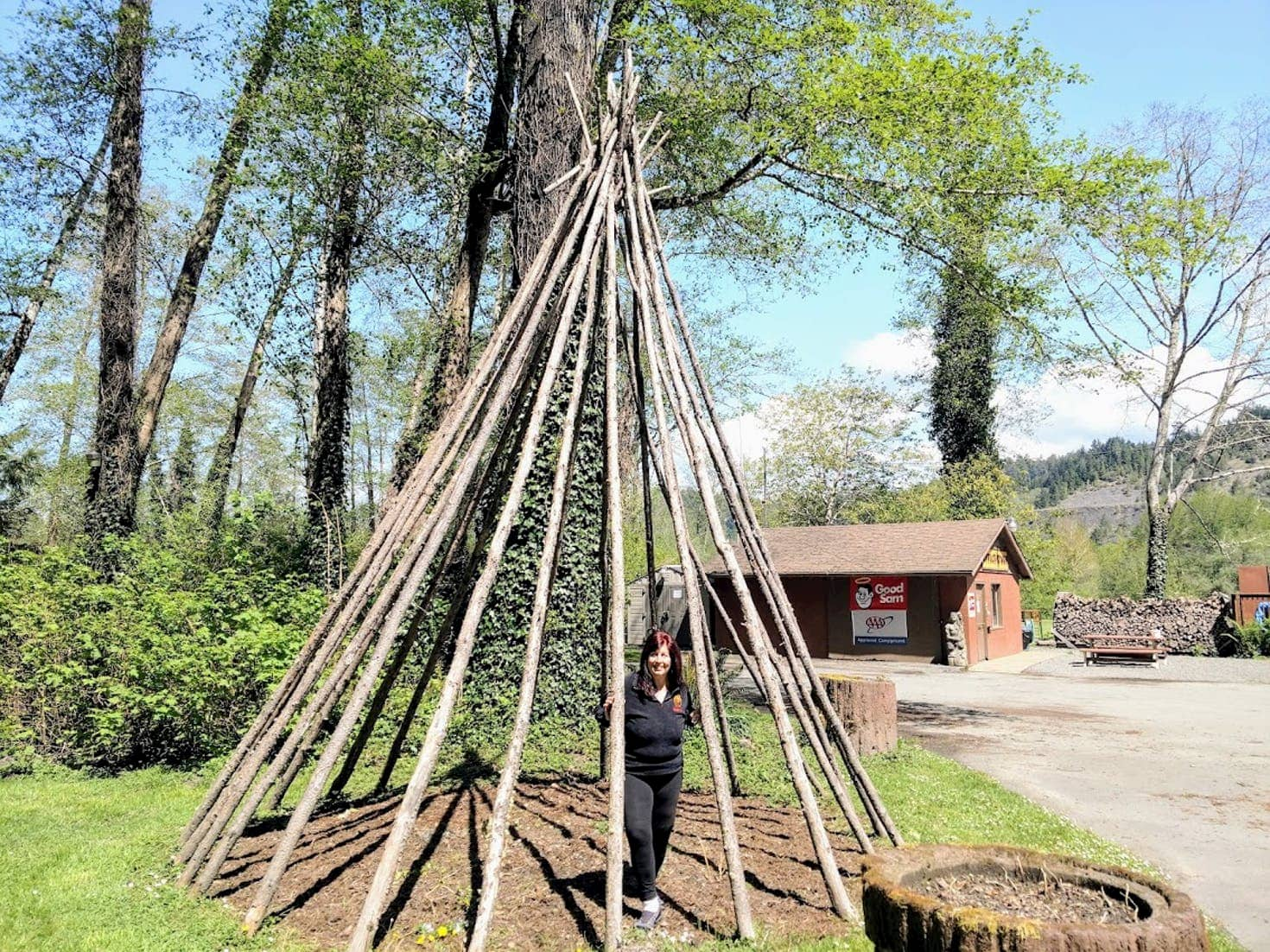 Women standing inside of a large teepee.