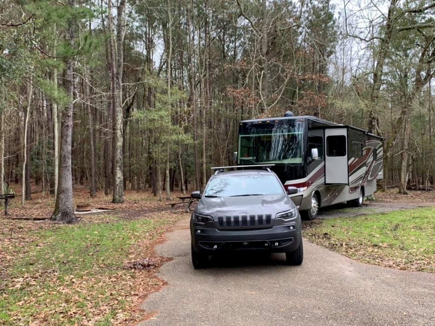 Black car parked in front of big rig RV at a forested campsite.