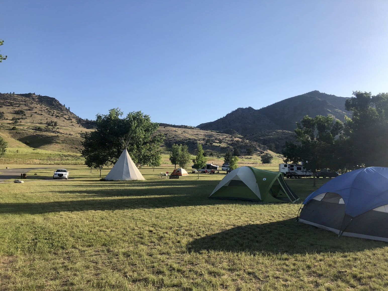 Assorted tents and glamping teepee set up in a field with mountains in the background.
