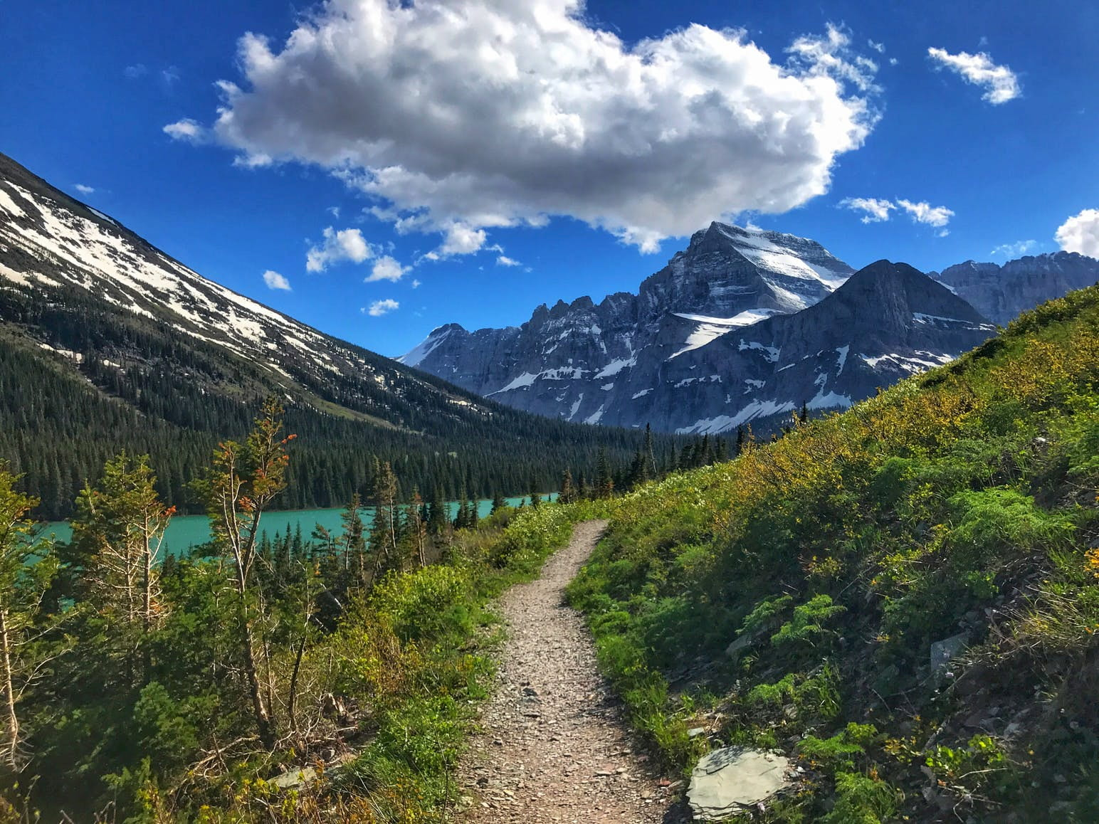 Hiking trail runs into mountainous landscape, beside bright blue glacial lake.