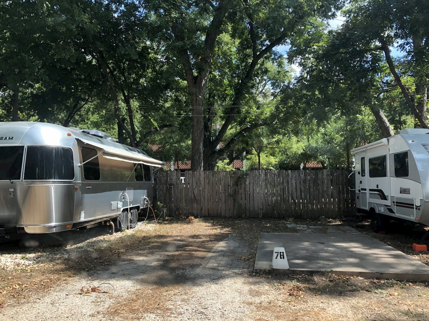 Two RVs parked beside picket fence at RV campground.