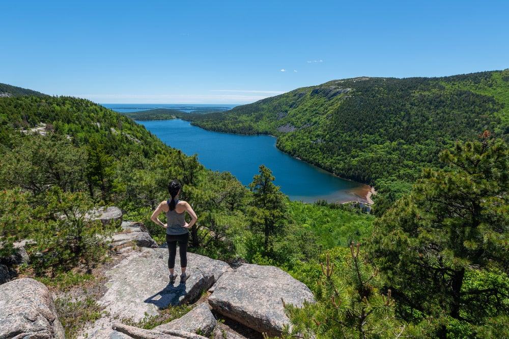 a hiker on the egde of a cliff in acadia national park