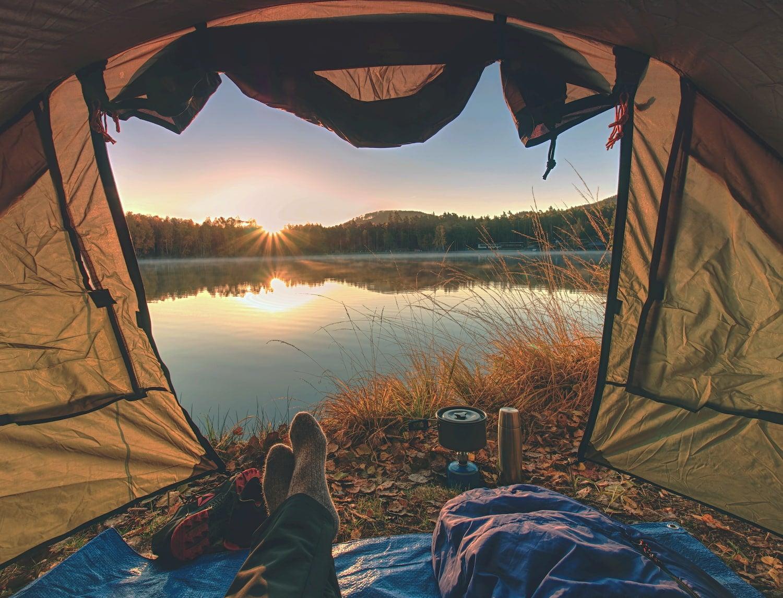 backpacker relaxing in tent with breakfast