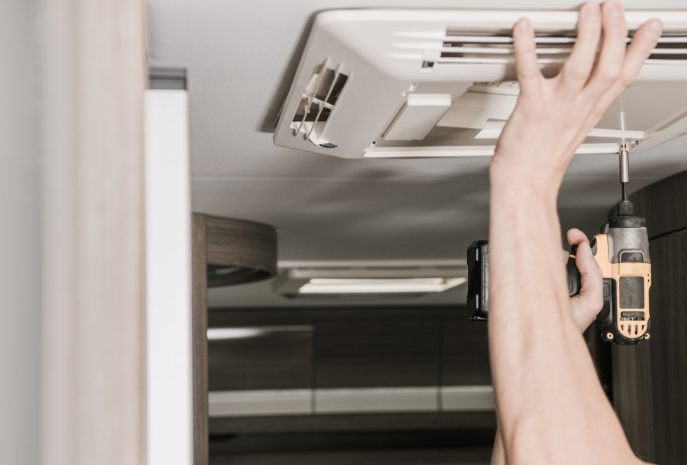 Person fixing RV air condtioner