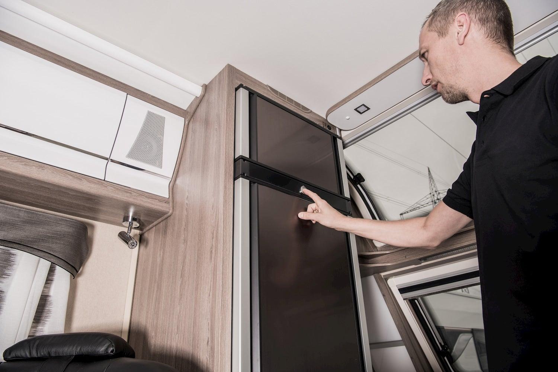 man touching fridge in rv