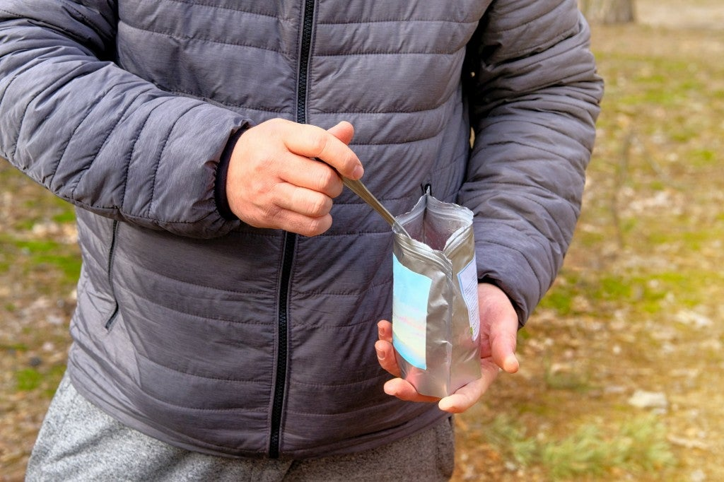 backpacker eating food out of a freeze dried bag