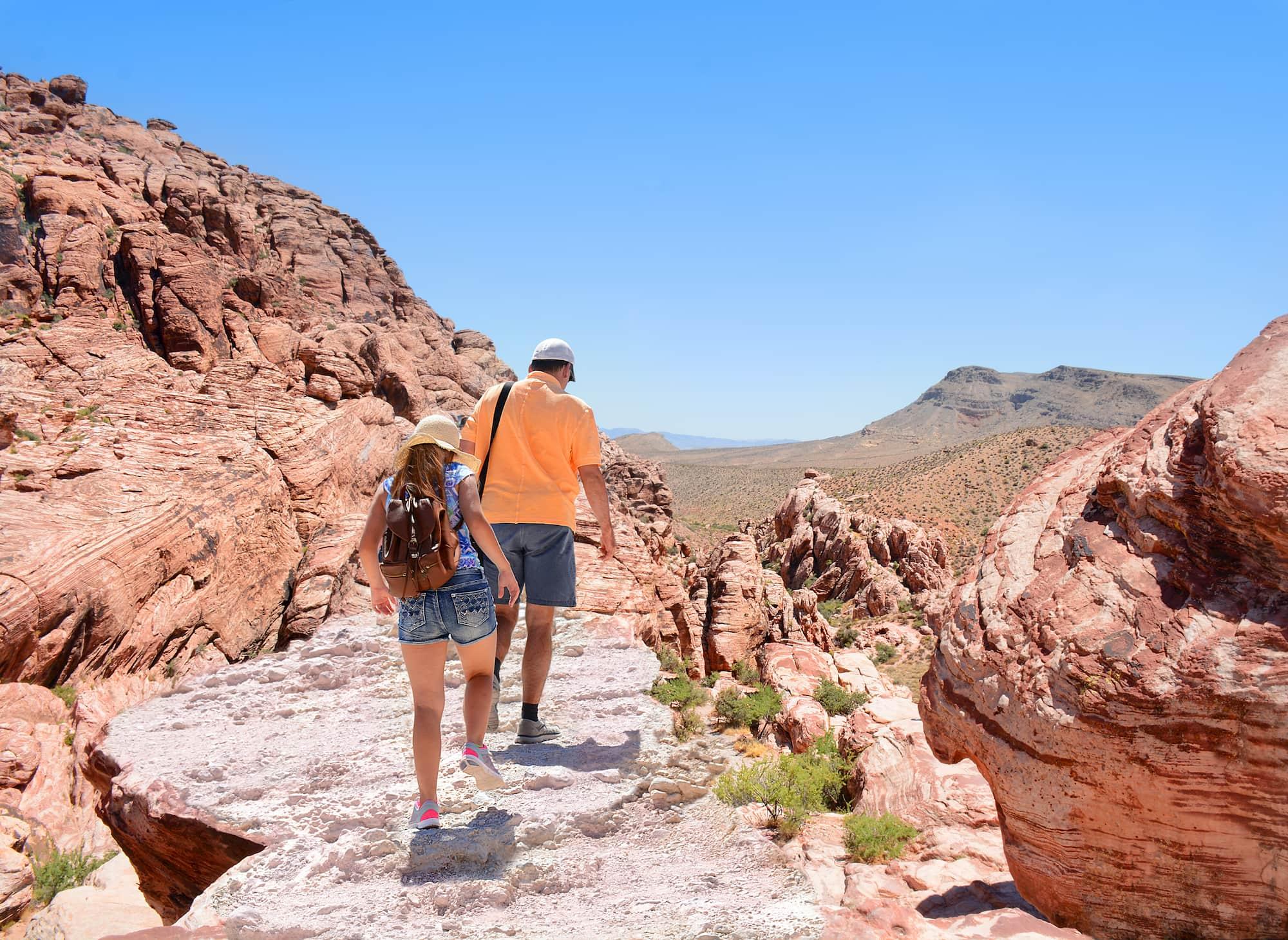 people hiking near red rocks