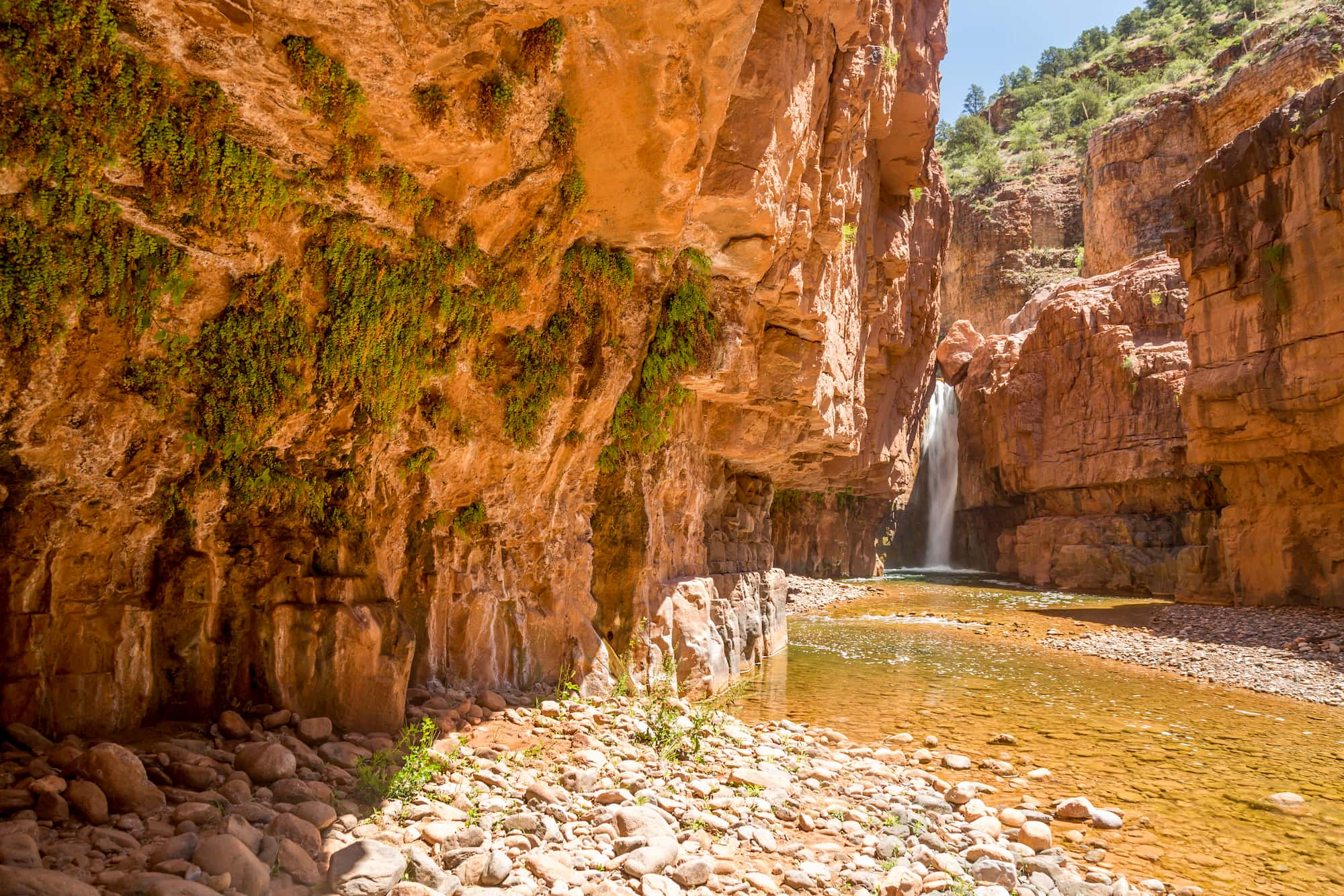 Waterfall flowing between red rock cliffs.