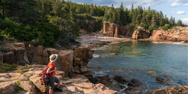 a hiker on the coast of maine hiking in acadia national park