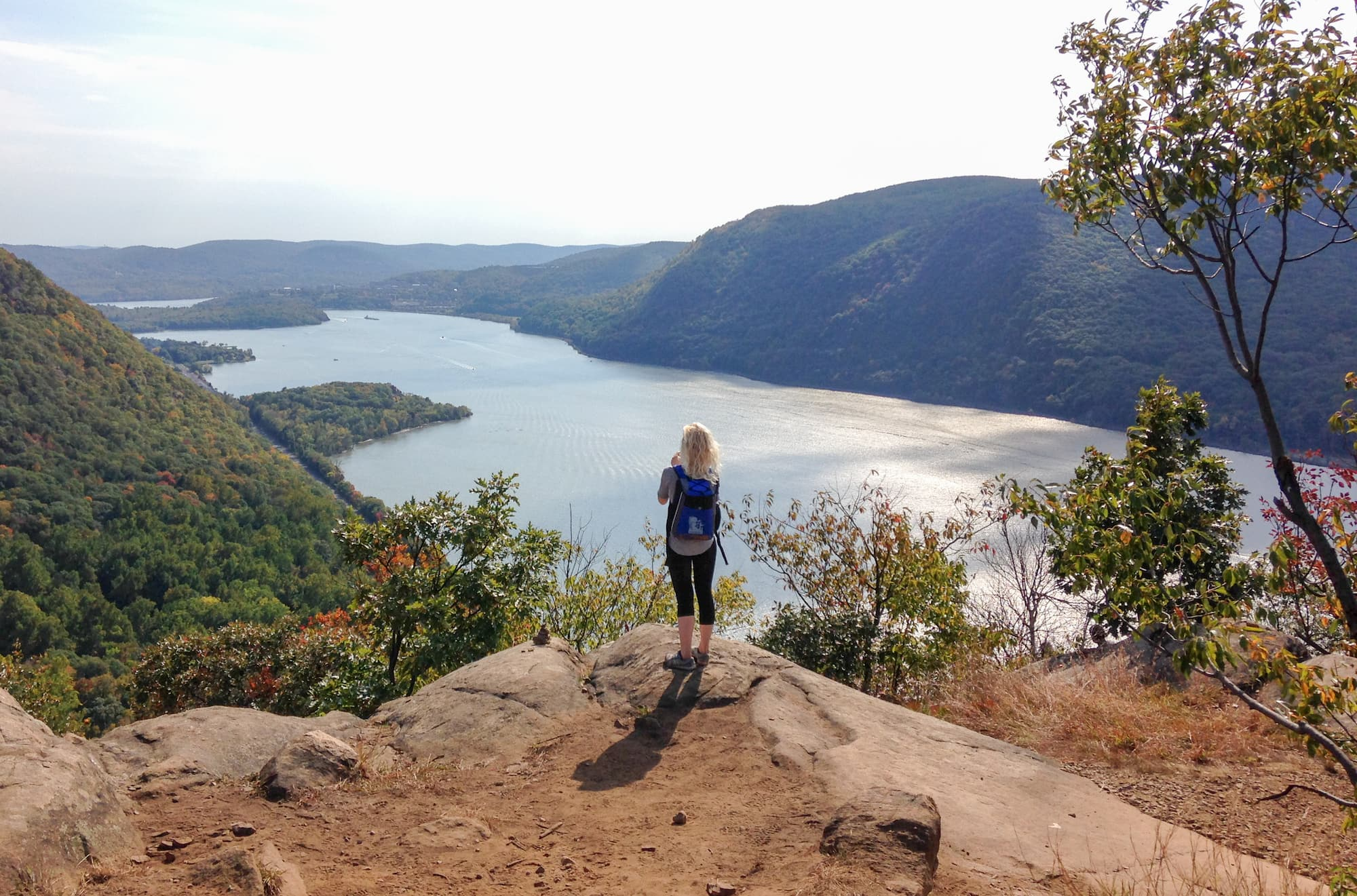 Female hiker standing over viewpoint in gorge with river flowing through.
