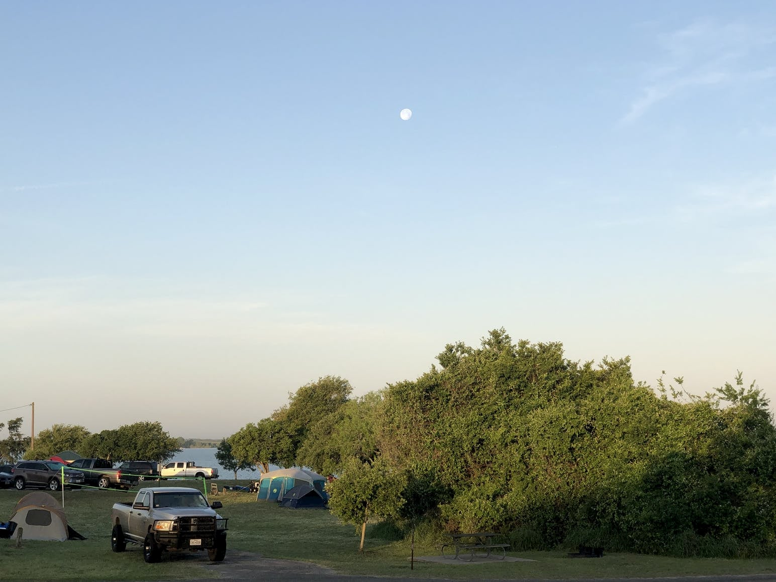 Cars parked beside tents at campground under a full moon.